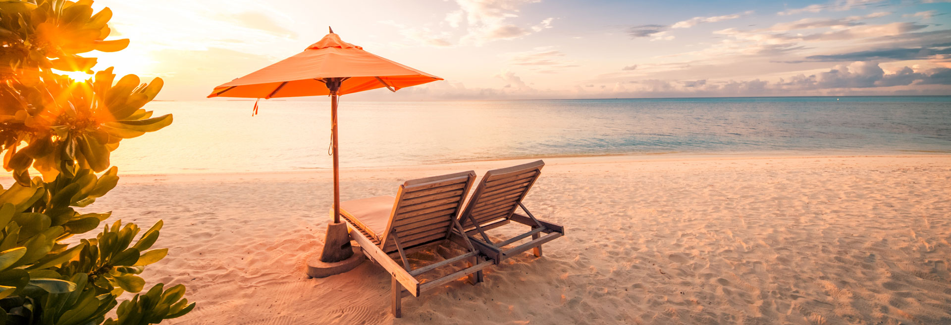 Wooden Beach Lounges with orange umbrella at the seaside escape of The Residences at The St. Regis Longboat Key Resort