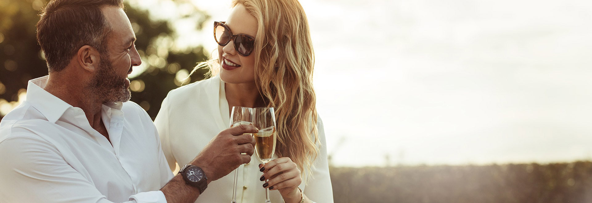 Couple holding champagne flutes enjoying seaside living at The Residences at The St. Regis Longboat Key Resort