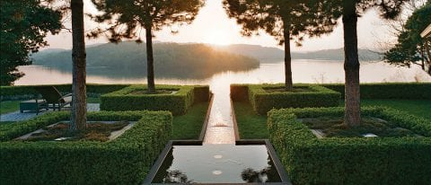 beautiful water feature that looks like it does out into a lake with islands in the background and the sun behind them