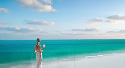 Woman on patio looking at ocean at The Residences at The St. Regis Longboat Key