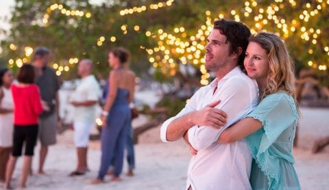 Couple hugging on the beach during an event with twinkling lights in the background