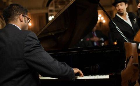 Man at piano entertaining guests at The Residences at The St. Regis Longboat Key