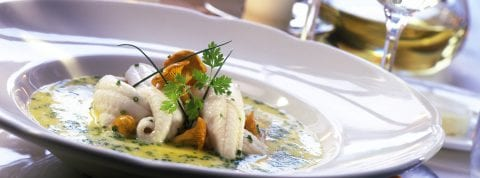 Succulent white fish in a butter sauce on a white plate served for dinner at The Residences at The St. Regis Longboat Key