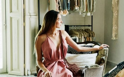 Woman in pink dress sitting in a chair at an upscale clothing store in Sarasota