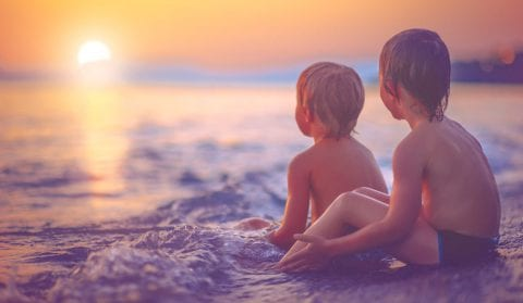 Two boys sitting in the surf at The Residences at The St. Regis Longboat Key