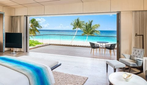 Bedroom with sliding glass door open to the patio and ocean below at The Residences at The St. Regis Longboat Key