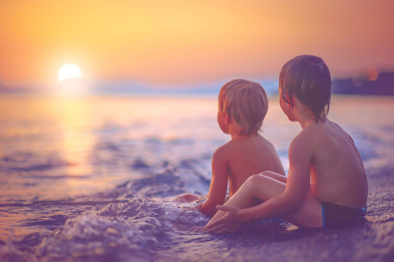 Kids sitting on the beach at Longboat Key