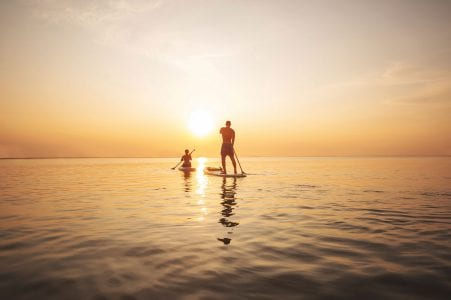 Paddleboarding on the ocean at dusk near The Residences at The St. Regis Longboat Key