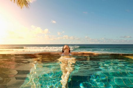Woman relaxing in one of the infinity pools at The Residences at The St. Regis Longboat Key