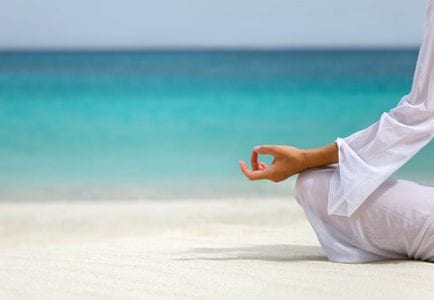 Woman seated on the sand practicing meditation at The Residences at The St. Regis Longboat Key Resort